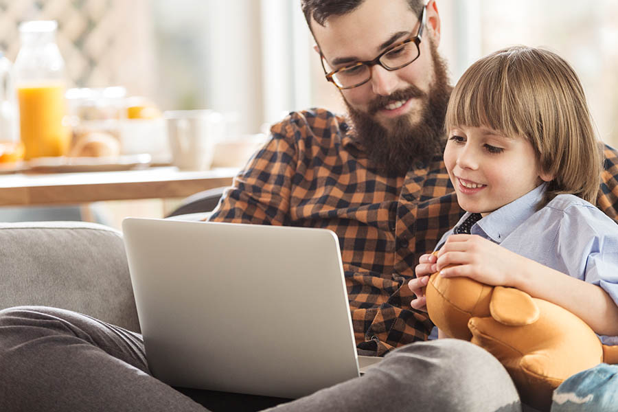 Client Tools - Father and Son Sitting Together on the Sofa While Father Looks at Account Information on Insurance