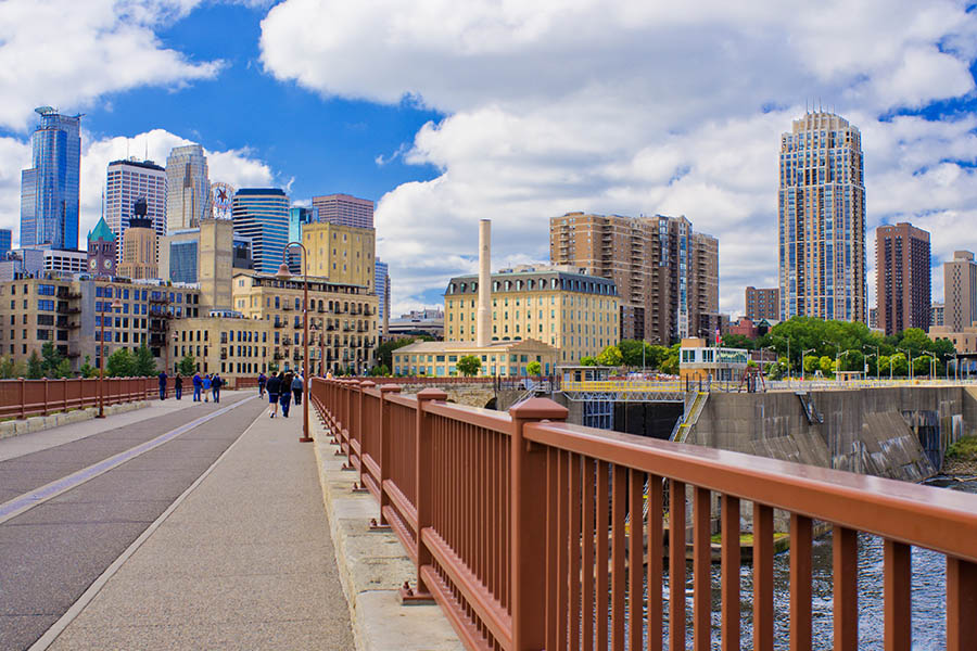 Minneapolis, MN - Minneapolis Skyline View From Across a Bridge with City, Clouds and Blue Sky in the Background
