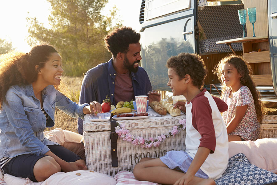 Personal Insurance - Family on Vacation Having a Picnic Outside at Dusk Beside their Camper